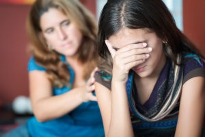 Teenager problems - Mother comforts her troubled teenage daughte